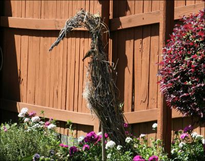 Garden sculpture of a heron, made of vines and grasses. A sparrow borrows some material for its nest.