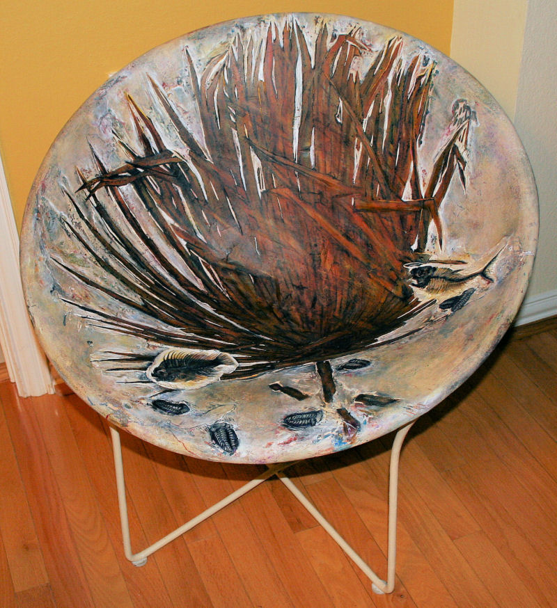 Cycad Leaf Fossil Chair, Homage to the history of Earth, 29 x 29 x 29 inches, refurbished vintage chair, woven canvas strips, plaster cured, sanded, carved, extinct Myalina fossils, acrylics, varnish, waxed. Functional, durable.